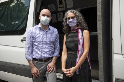 Two adults in masks in front of van